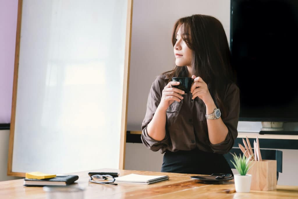 woman holding coffee looking out window thinking about fundraising jobs